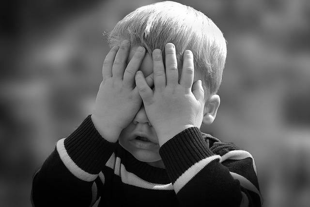 dziecko osłania twarz dłońmi
