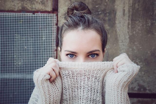 kobieta wygląda zza swetra