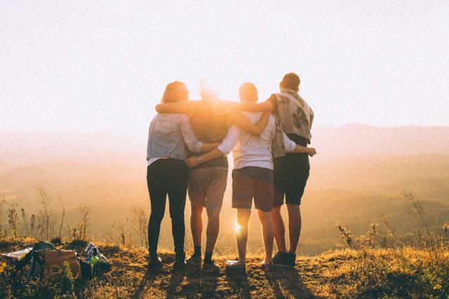 Grupa ludzi na tle słońca