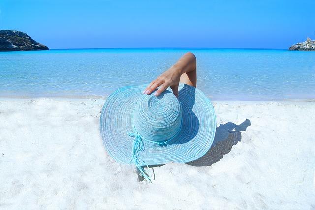 Kobieta w kapeluszu leży nad morzem
