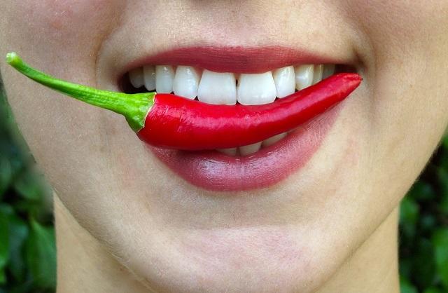 Kobieta z papryczką chilli w ustach