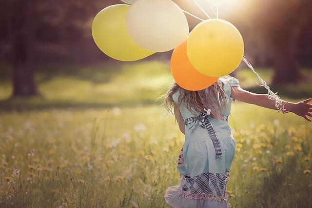 dziewczynka biegnie z balonami